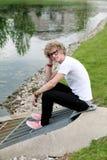Type s'asseyant à l'extérieur par le lac Image libre de droits