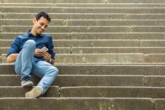Type s'asseyant sur des escaliers avec le smartphone photo stock