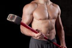 Type sans chemise retenant un marteau de forgeron photos stock