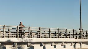 Type se tenant sur le pont et appréciant la nature Photo libre de droits
