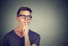 Type secret Équipez dire que le silence soit tranquille avec le doigt sur le geste de lèvres regardant au côté images libres de droits