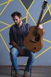 Type songeur avec une guitare photographie stock libre de droits