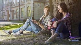 Type sous l'arbre regardant la fille s'asseyant à côté de lui, amour aux premiers sentiments de vue Image stock