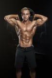 Type sportif beau posant avec le plat de barbell Image stock