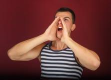 Type sportif dans les hurlements de chemise rayée photographie stock libre de droits