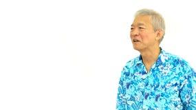 Type supérieur asiatique heureux sur la chemise bleue d'Hawaï regardant de côté sur le whi Photographie stock libre de droits