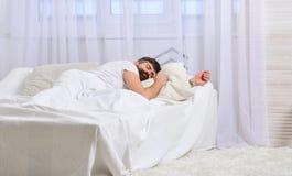 Type sur le visage calme dormant sur les feuilles blanches, oreiller Concept de petit somme et de sièste Équipez la pose sur le l Photographie stock libre de droits