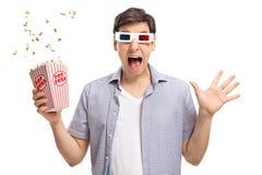 Type terrifié avec une paire de verres 3D et de maïs éclaté Image libre de droits