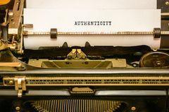 Type writer and paper, word authenticity. Written in bold letter stock images
