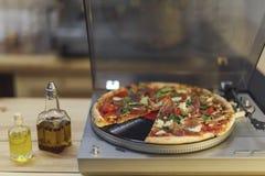 Typer av olja i flaskor och italiensk pizza på vinylskivspelaren Royaltyfri Foto