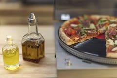 Typer av olja i flaskor och italiensk pizza på vinylskivspelaren Royaltyfri Bild