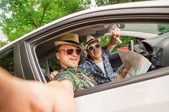 Types à la mode de hippie s'asseyant dans la voiture et prenant le selfie Images libres de droits