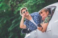 Types à la mode hors des fenêtres de voiture utilisant des téléphones portables dehors Photo libre de droits