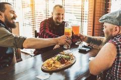 Types adultes heureux appréciant la bière blonde allemande froide Photos libres de droits