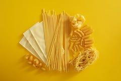 Types assortis de pâtes sur le fond jaune Image stock