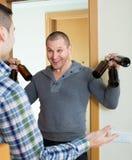 Types avec des bouteilles à bière à la porte Photo stock