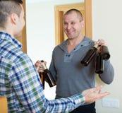 Types avec des bouteilles à bière à la porte Image stock