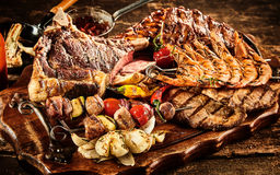 Types of barbecued beef. Various types of barbecued beef and seafood with roasted tomatoes and potatoes over wooden table background stock photo