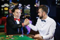Types beaux jouant la roulette dans le casino Photographie stock libre de droits