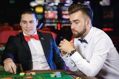 Types beaux jouant la roulette dans le casino Images stock