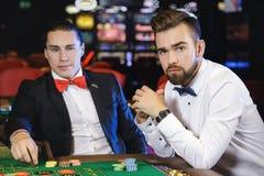 Types beaux jouant la roulette dans le casino Photos stock