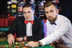 Types beaux jouant la roulette dans le casino Photos libres de droits