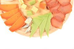 Types of cheese and meat on wooden platter. Royalty Free Stock Images