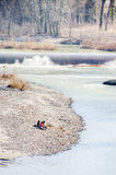 Types d'amis s'asseyant par cascade d'hiver de rivière la petite Photos libres de droits