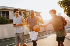 Types de basket-ball marchant sur la rue jouant avec la boule Images libres de droits