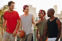 Types de basket-ball marchant sur le trottoir avec la boule Image libre de droits