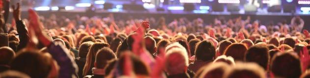 Types et filles de l'assistance pendant le concert vivant Photographie stock libre de droits