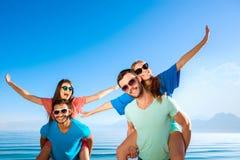 Types et filles heureux à la station de vacances Image stock
