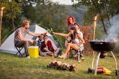Types et gamines tapant avec des bouteilles et de la bière dans le terrain de camping Images stock
