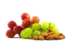 Types of grapes and almonds. Some red and green grapes and some almonds on a white background Royalty Free Stock Photography