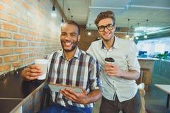 Types heureux détendant dans le cafétéria Photo libre de droits