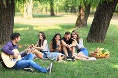 Types heureux et filles ayant l'amusement avec la guitare, chantant, riant Photos stock