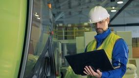 Types masculins d'ingénieur sur un ordinateur portable, se tenant dans une installation, équipement d'usine banque de vidéos