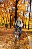 Types montant le vélo en parc d'automne Image libre de droits