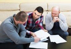 Types s'asseyant avec des papiers Photos stock