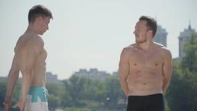 Types sportifs ayant l'amusement dehors Hommes démontrant des muscles entre eux Personnes sportives avec le repos chaud de corps banque de vidéos