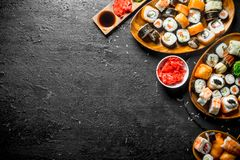 Types of sushi, Maki and rolls served on plates. On black rustic background royalty free stock photo