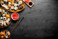 Types of sushi, Maki and rolls served on plates. On black rustic background royalty free stock photos