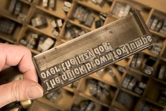 Typesetter's composing stick. Typesetter's hand holding composing stick with drawer containing letterpress characters in background royalty free stock photos