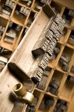 Typesetter's composing stick. Composing stick with drawer containing letterpress characters in background (focus on composing stick royalty free stock photography