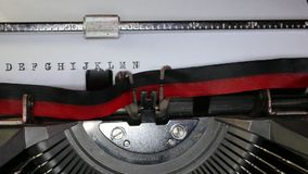 TYPEWRITER with alphabet in the paper. Old typewriter with alphabet with black ink in paper stock video