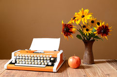 Typewriter apples and flowers in a vase Stock Photo