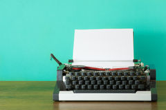 Typewriter with blank page. White paper page in a old retro typewriter on a wooden desk Stock Image