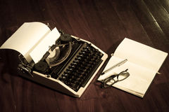 Typewriter with book and eyeglasses Stock Image