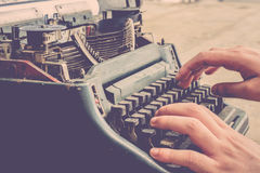 Typewriter and human hand. Vintage typewriter and human hand on a wood table , process in vintage style Royalty Free Stock Images
