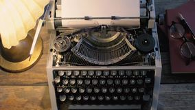 Typewriter lit by a table lamp stock video